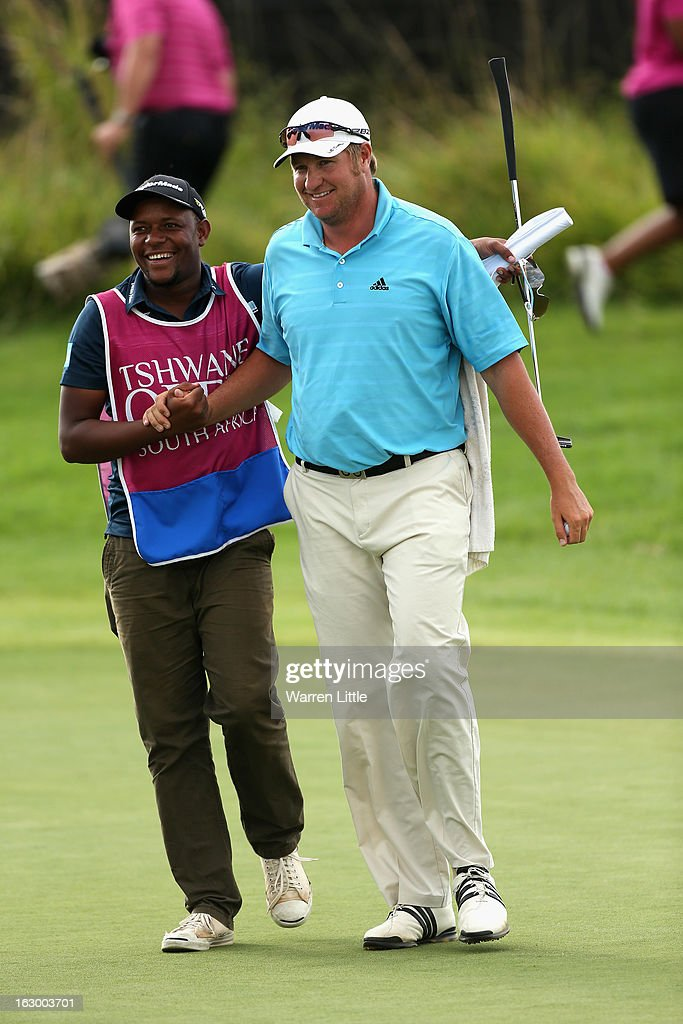 Dawie Van Der Walt of South Africa is congratulated by his caddie on the 18th green after winning the Tshwane Open at Copperleaf Golf & Country Estate on March 3, 2013 in Centurion, South Africa.