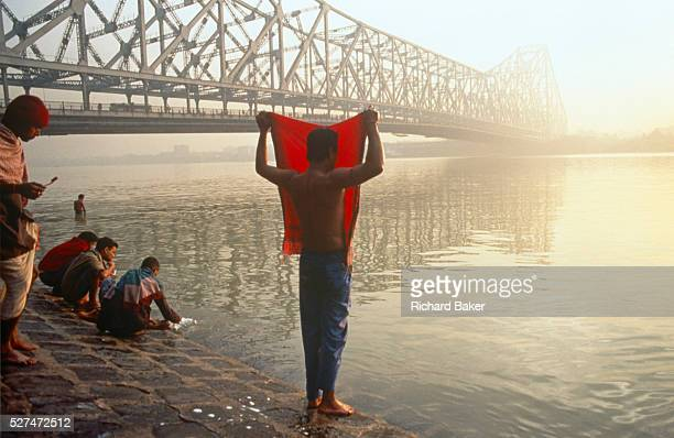A dawn bather covers his face with red cloth as sun rises over Hooghler River KolIkata It is dawn in Calcutta West Bengal India and on the West bank...