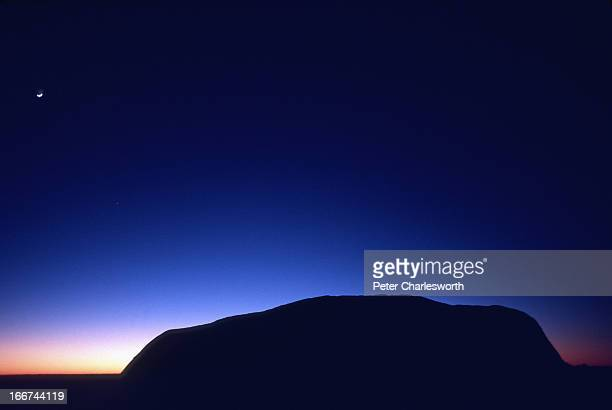 Dawn breaks at Ayers Rock with a nighttime star shining above one of Australia's most famous landmarks one of the most sacred places in the Outback...
