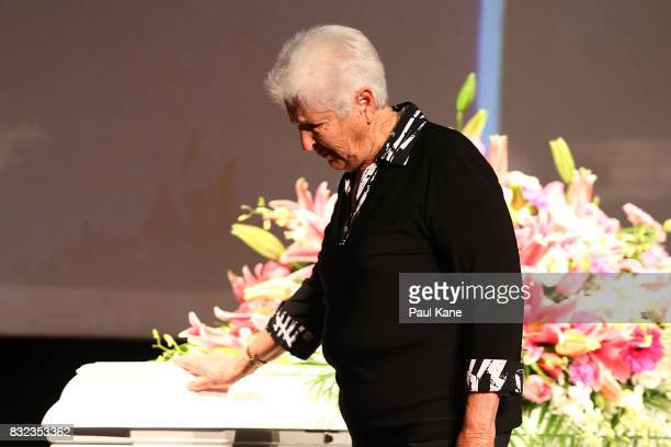 Dawn Fraser places her hand on the coffin after delivering a eulogy during the funeral service for Betty Cuthbert at Mandurah Performing Arts Centre...