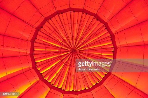 Dawn illuminates the vents of an inflated hot air balloon.