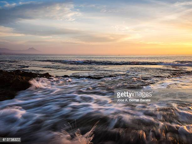 Dawn in an area of rocky coastline with waves moving and swirling water