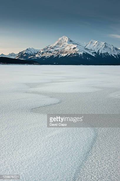 Dawn light hits Elliot Peak on a snow covered and frozen Abraham Lake, Canadian Rockies, Alberta, Canada