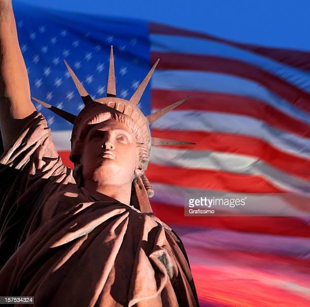 Amanecer sobre Estatua de la libertad y de la bandera estadounidense