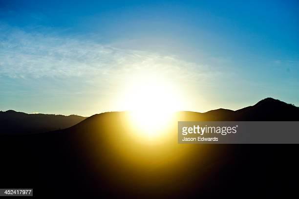 Dawn rises over a mountain ridge-line beneath a clear blue sky.