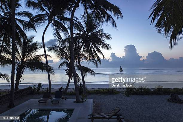 Dawn view of the Indian ocean at Msambweni a fisherman's boat in the distance A European's holiday residence swimming pool and palms are in the...