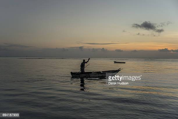 Dawn view of the Indian ocean at Msambweni a fishermen in his dugout canoe waves as he sets off to catch the high tide The small fishing town and...