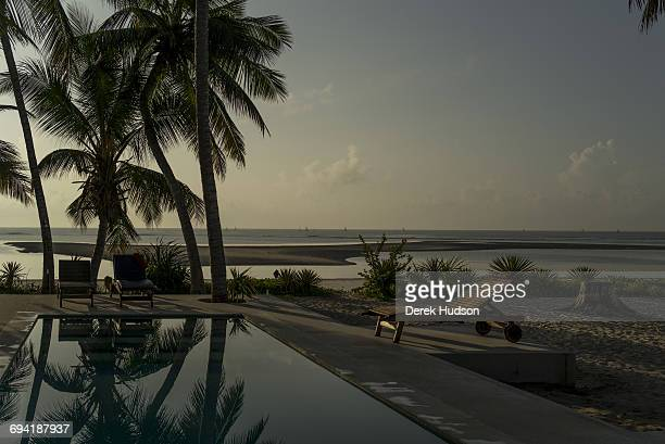 Dawn view of the Indian ocean at Msambweni fishing boats on the distant horizon A European's holiday residence swimming pool and palms are in the...