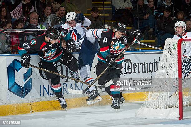 Dawson Davidson of the Kamloops Blazers is checked by Calvin Thurkauf and Nick Merkley of the Kelowna Rockets behind the net during second period on...