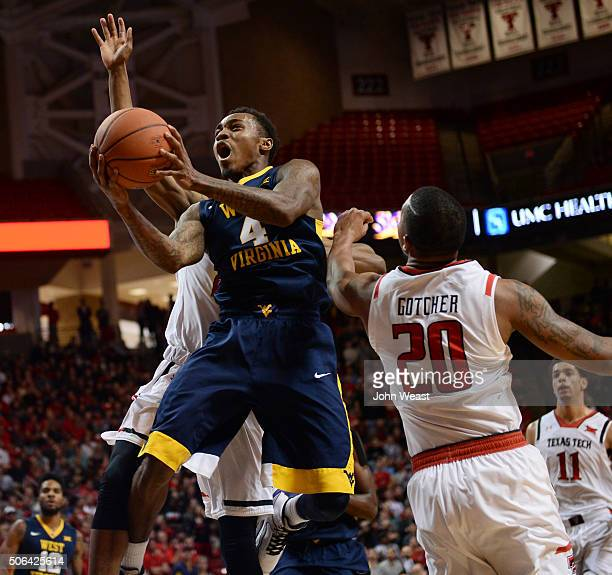 Daxter Miles Jr #4 of the West Virginia Mountaineers goes to the basket against Toddrick Gotcher of the Texas Tech Red Raiders during the first half...
