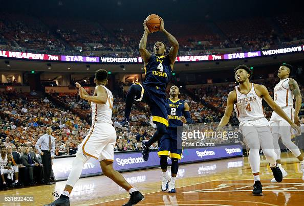Daxter Miles Jr #4 of the West Virginia Mountaineers shoots between Eric Davis Jr #10 and James Banks of the Texas Longhorns at the Frank Erwin...