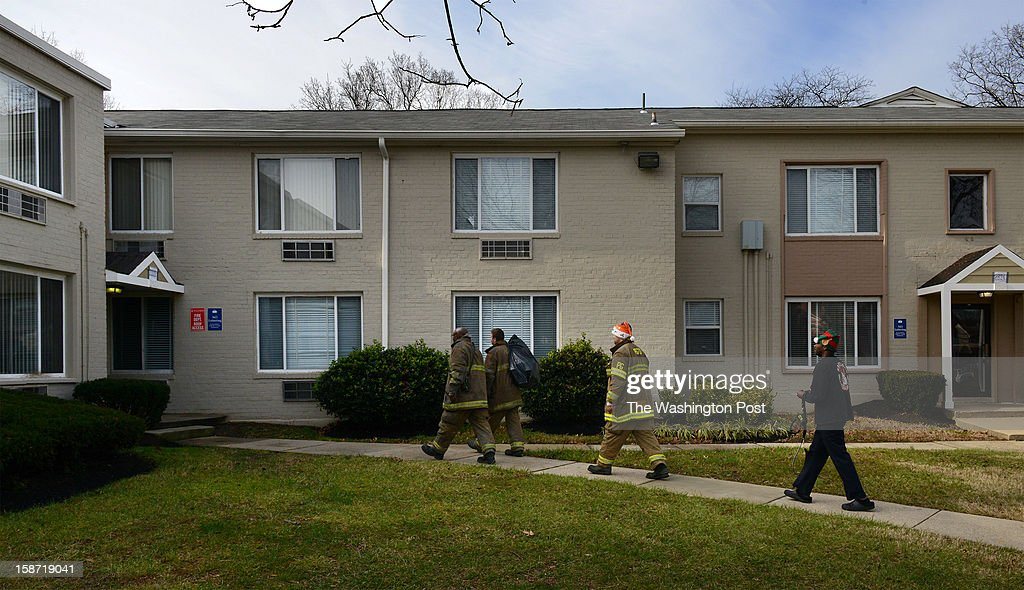 A day after four firefighters were ambushed and shot in upstate NY, firefighters approach an apartment building with a bag of toys from Toys for Tots that they are trying to deliver from Kentlands volunteer fire department on December, 25, 2012 in Landover, MD.