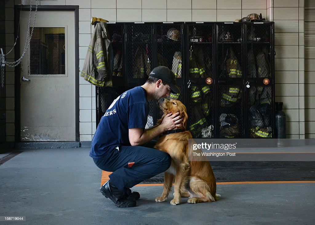 A day after four firefighters were ambushed and shot in upstate NY, firefighter Kevin Stapleton greets Murphy, the golden retriever who lives at Kentlands volunteer fire department on December, 25, 2012 in Landover, MD.