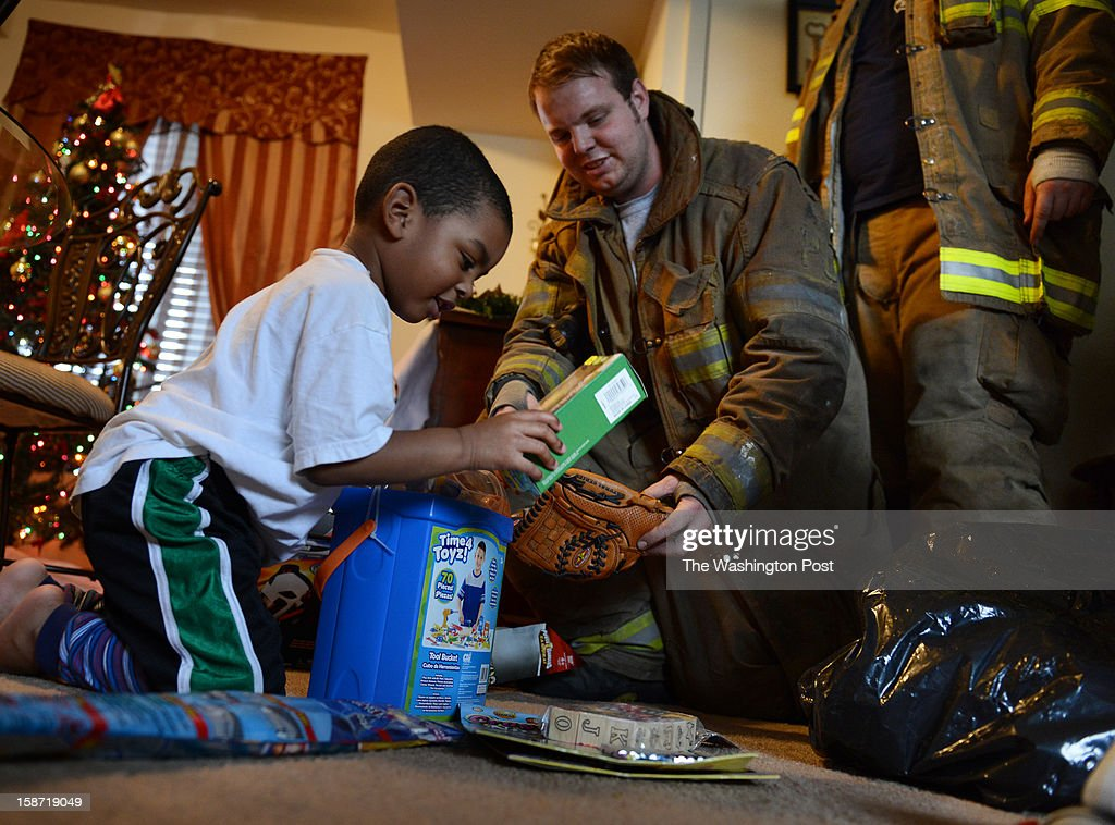 A day after four firefighters were ambushed and shot in upstate NY, firefighter Keith Trickle delivers gifts from the Toys for Tots program to Nathan Cobbs, 3, on December, 25, 2012 in Landover, MD.