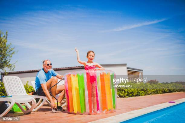 Day Dreaming At The Swimming Pool - Father Pumping Water Heel Toy For His Daughter