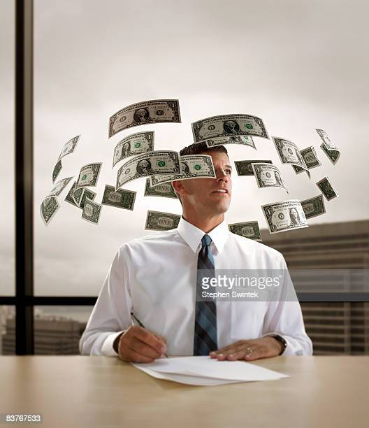 A day dreaming businessman with money swirling