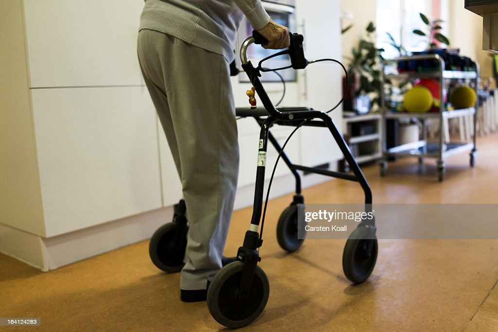 A day guest crosses the room in the geriatric day care facility of the German Red Cross (DRK, or Deutsches Rotes Kreuz) at Villa Albrecht on March 18, 2013 in Berlin, Germany. A great number of senior Citzens struggle with various forms of dementia at Villa Albrecht. The German Red Cross dates its origin back to 1863 with the founding of the Wuerttembergischer Sanitaetsverein, a medical association that provided care to wounded soldiers. Today the German Red Cross has four million members nationwide and is active in international aid and social care.