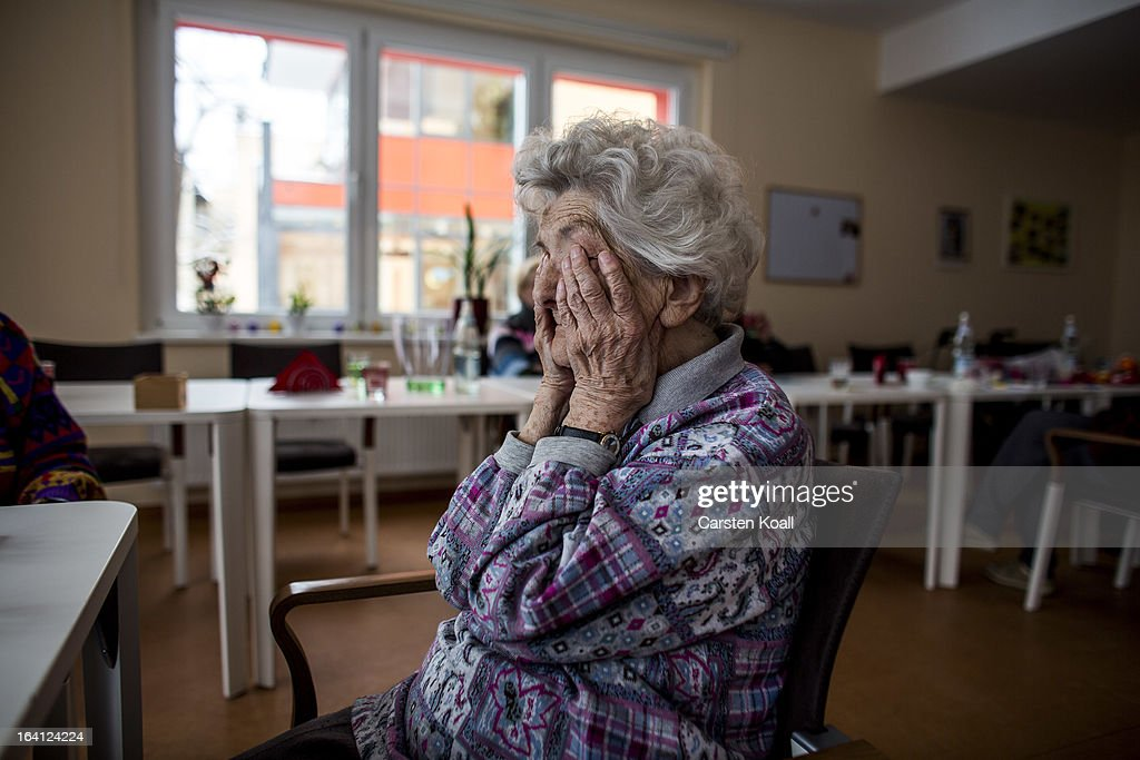 Day guest Helga covered her face with her hands the middle of the room in the geriatric day care facility of the German Red Cross at Villa Albrecht...