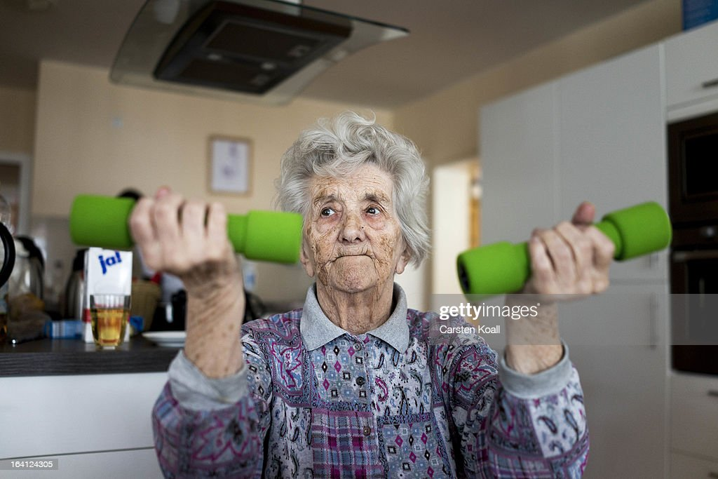 Day guest Helga lifts dumbbells during a sport lesson in the geriatric day care facility of the German Red Cross (DRK, or Deutsches Rotes Kreuz) at Villa Albrecht on March 18, 2013 in Berlin, Germany. A great number of senior Citzens struggle with various forms of dementia at Villa Albrecht. The German Red Cross dates its origin back to 1863 with the founding of the Wuerttembergischer Sanitaetsverein, a medical association that provided care to wounded soldiers. Today the German Red Cross has four million members nationwide and is active in international aid and social care.