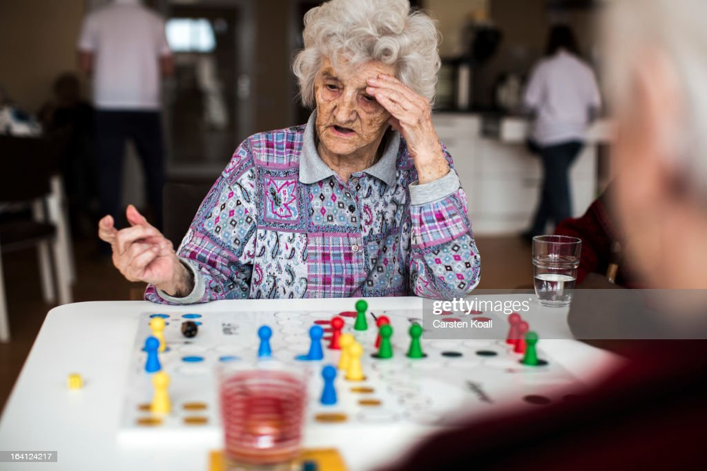 Day guest Helga plays the game Ludoin the geriatric day care facility of the German Red Cross at Villa Albrecht on March 11 2013 in Berlin Germany A...