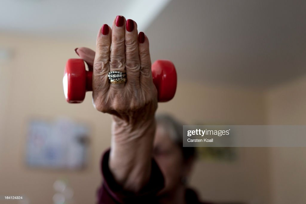 A day guest lifts dumbbells during a sport lesson in the geriatric day care facility of the German Red Cross (DRK, or Deutsches Rotes Kreuz) at Villa Albrecht on March 18, 2013 in Berlin, Germany. A great number of senior Citzens struggle with various forms of dementia at Villa Albrecht. The German Red Cross dates its origin back to 1863 with the founding of the Wuerttembergischer Sanitaetsverein, a medical association that provided care to wounded soldiers. Today the German Red Cross has four million members nationwide and is active in international aid and social care.