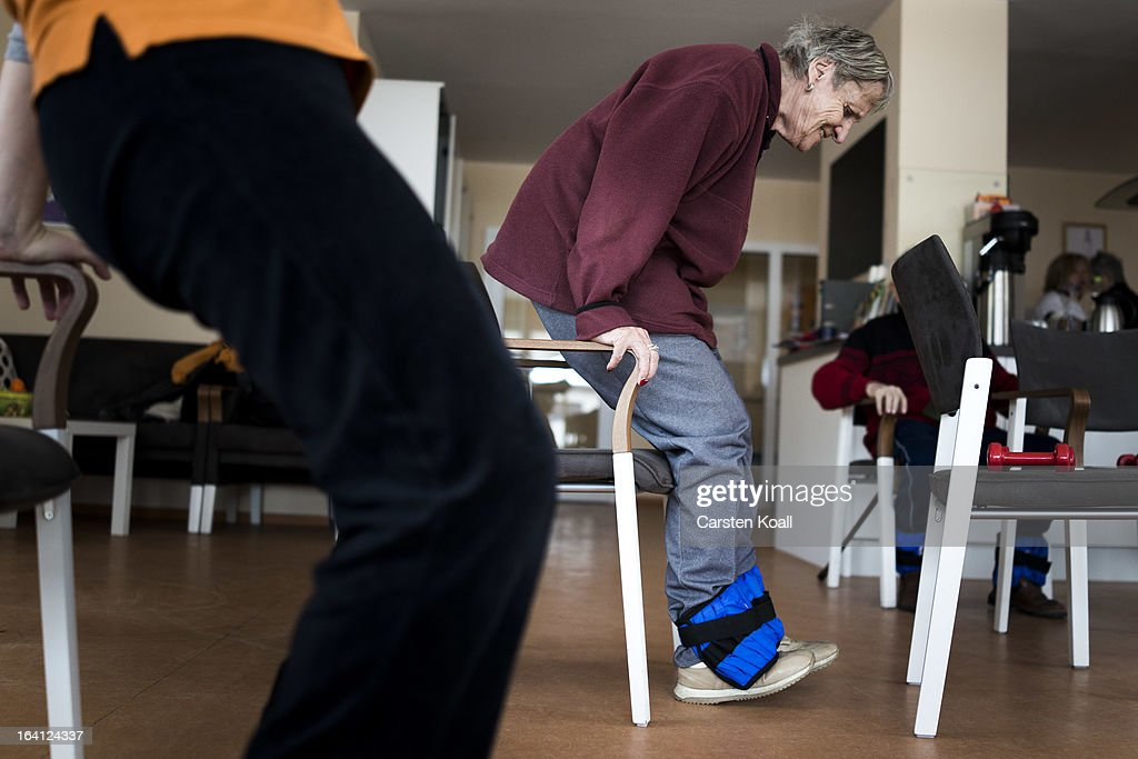 A day guest makes a gymnastic exercise during a sport lesson in the geriatric day care facility of the German Red Cross (DRK, or Deutsches Rotes Kreuz) at Villa Albrecht on March 18, 2013 in Berlin, Germany. A great number of senior Citzens struggle with various forms of dementia at Villa Albrecht. The German Red Cross dates its origin back to 1863 with the founding of the Wuerttembergischer Sanitaetsverein, a medical association that provided care to wounded soldiers. Today the German Red Cross has four million members nationwide and is active in international aid and social care.