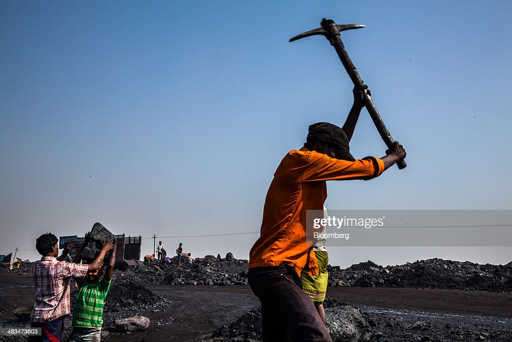 A day laborer breaks coal using a pick at an open pit coal mine in the Bestacolla Colliery in Jharia, Jharkhand, India, on Sunday, April 6, 2014. Coal India Ltd., the worlds largest producer, estimates on its website that the nation faces a supply deficit of 350 million tons by 2016-2017, thereby overtaking import demand from China, the worlds biggest coal consumer and producer. Photographer: Sanjit Das/Bloomberg via Getty Images
