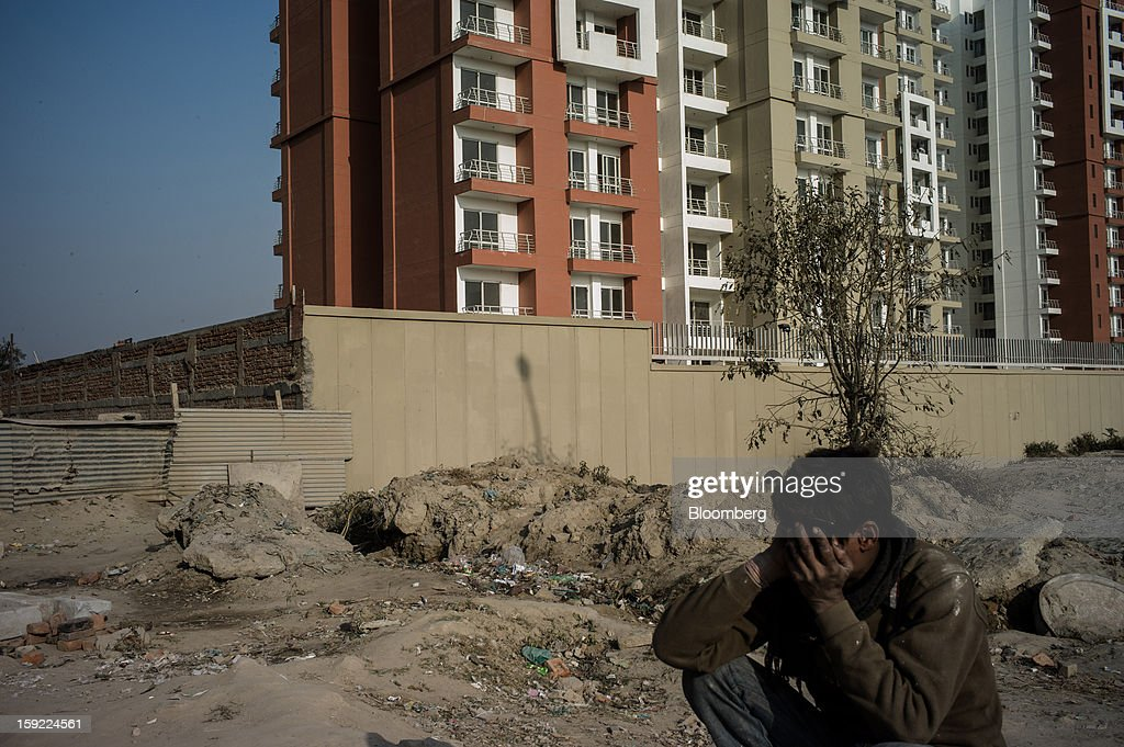 A day laborer speaks on a mobile phone outside a completed apartment block in Noida, Uttar Pradesh, India, on Wednesday, Jan. 9, 2013. India's Finance Ministry predicts GDP growth of as little as 5.7 percent in the year to March 31, the least in a decade. Photographer: Sanjit Das/Bloomberg via Getty Images