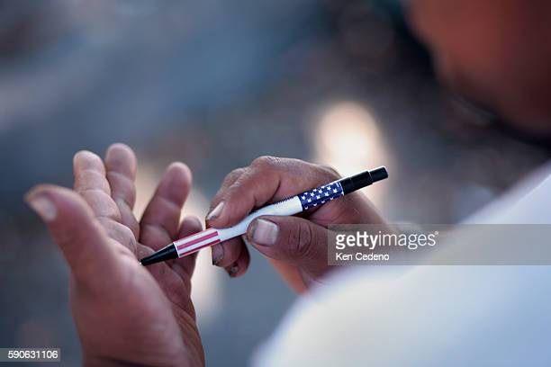 A Day Laborer writes on his hand with an American Flag pen outside a Home Depot in San Diego hang out waiting for possible work to come their way on...