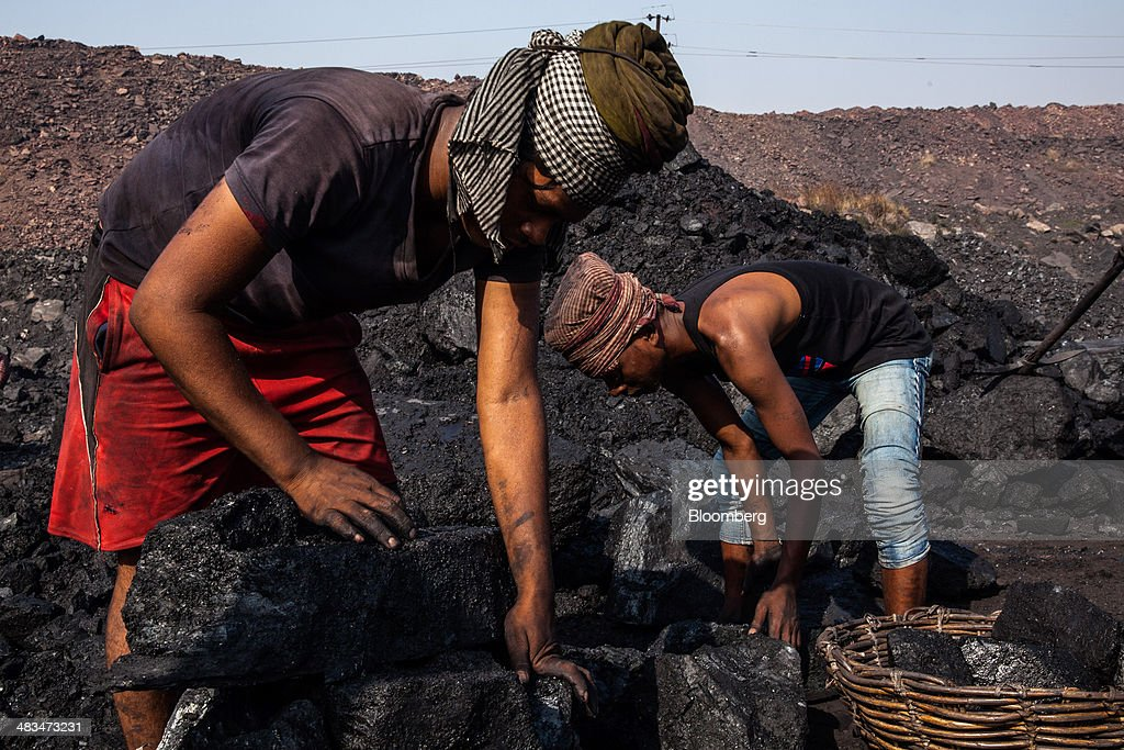 Day laborers breaks place coal in baskets at an open pit coal mine in the Bestacolla Colliery in Jharia, Jharkhand, India, on Sunday, April 6, 2014. Coal India Ltd., the worlds largest producer, estimates on its website that the nation faces a supply deficit of 350 million tons by 2016-2017, thereby overtaking import demand from China, the worlds biggest coal consumer and producer. Photographer: Sanjit Das/Bloomberg via Getty Images