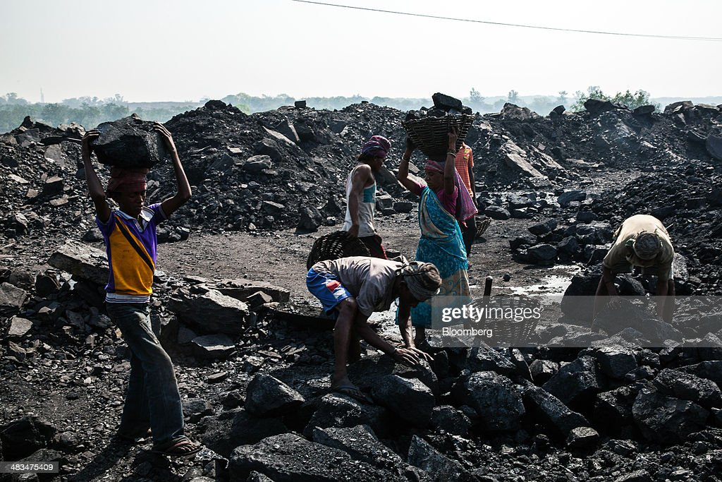 Day laborers fill baskets with coal at an open pit coal mine in the Bestacolla Colliery in Jharia, Jharkhand, India, on Sunday, April 6, 2014. Coal India Ltd., the worlds largest producer, estimates on its website that the nation faces a supply deficit of 350 million tons by 2016-2017, thereby overtaking import demand from China, the worlds biggest coal consumer and producer. Photographer: Sanjit Das/Bloomberg via Getty Images