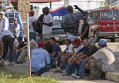 Day laborers gather outside the Lowe's construction supply store 30 August 2007 in New Orleans Louisiana New Orleans 29 August mourned the huge...
