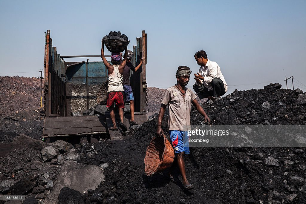 Day laborers load coal into trucks at an open pit coal mine in the Bestacolla Colliery in Jharia, Jharkhand, India, on Sunday, April 6, 2014. Coal India Ltd., the worlds largest producer, estimates on its website that the nation faces a supply deficit of 350 million tons by 2016-2017, thereby overtaking import demand from China, the worlds biggest coal consumer and producer. Photographer: Sanjit Das/Bloomberg via Getty Images