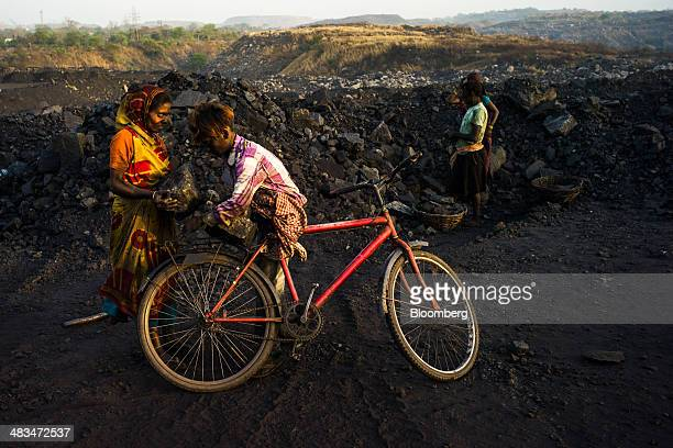Day laborers load coal onto a bicycle at the Goladi coal depot operated by Coal India Ltd subsidiary Bharat Coking Coal Ltd in Jharia Jharkhand India...