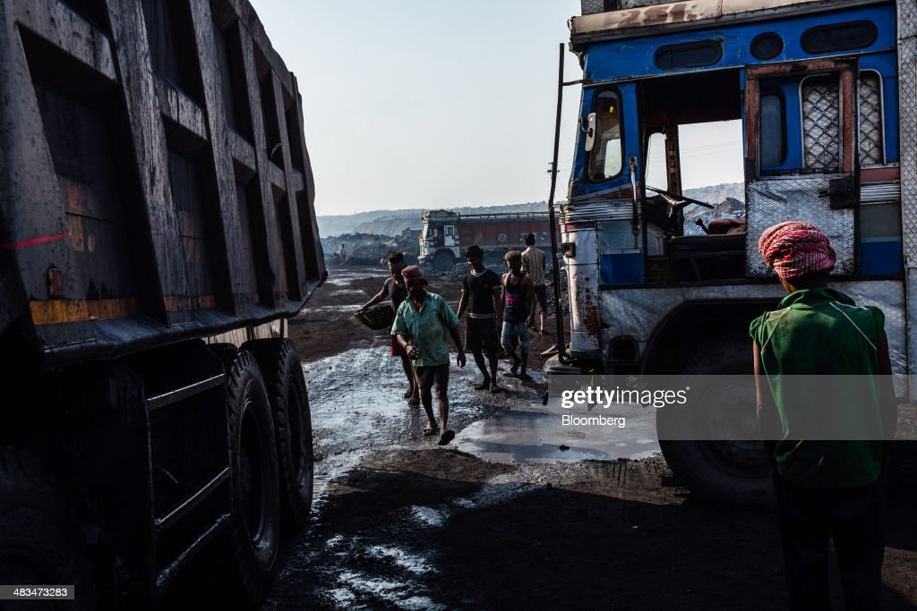 Day laborers walk towards trucks at an open pit coal mine in the Bestacolla Colliery in Jharia, Jharkhand, India, on Sunday, April 6, 2014. Coal India Ltd., the worlds largest producer, estimates on its website that the nation faces a supply deficit of 350 million tons by 2016-2017, thereby overtaking import demand from China, the worlds biggest coal consumer and producer. Photographer: Sanjit Das/Bloomberg via Getty Images