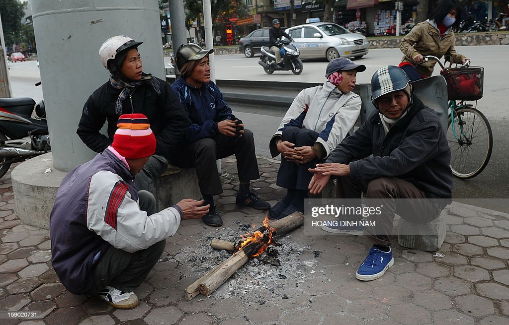 Day labourers waiting for work sit around a fire to keep warm on a street in downtown Hanoi on January 6, 2013 as northern Vietnam faces the toughest cold wave so far this season. Tempetures have dropped below 0 C (32F) in some mountainous areas bordering with China and elementary schools have been closed since January 4. AFP PHOTO / HOANG DINH Nam