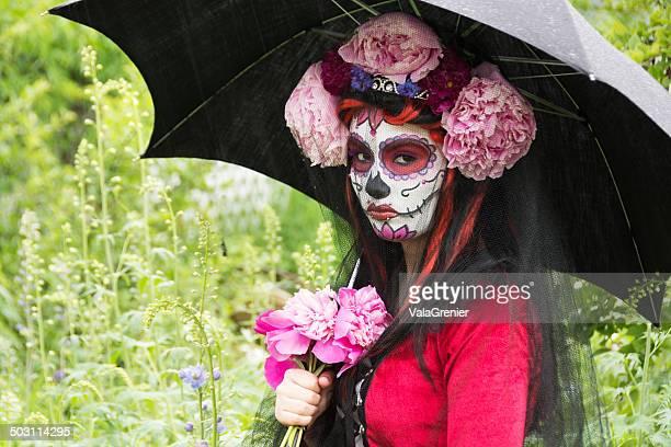 Day of the Dead bride with black umbrella.