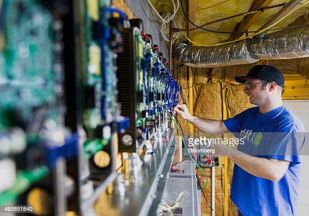 Day trader Jason Hughes works on running electoral wiring to junction boxes used to convert captured solar energy to store in Tesla Motors Inc...