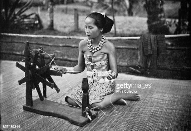 A Dayak girl at her spinning wheel 1902From The Living Races of Mankind Vol I [Hutchinson Co London 1902] Artist Unknown
