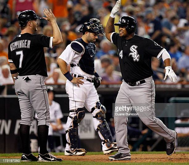Dayan Viciedo of the Chicago White Sox right celebrates his threerun home run with Jeff Keppinger after crossing the plate in front of catcher Alex...
