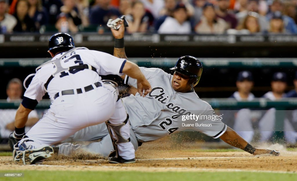 Dayan Viciedo #24 of the Chicago White Sox slides at home plate as Alex Avila #13 of the Detroit Tigers tries to make the tag in the seventh inning at Comerica Park on April 21, 2014 in Detroit, Michigan. Viciedo was called out on the play but a challenge overturned the call, giving the White Sox a 3-1 lead.