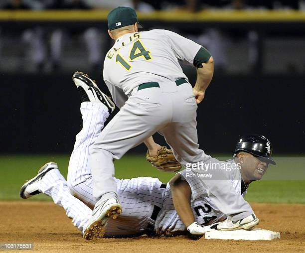 Dayan Viciedo of the Chicago White Sox slides back safely into second base under the tag of Mark Ellis of the Oakland Athletics on July 30 2010 at US...