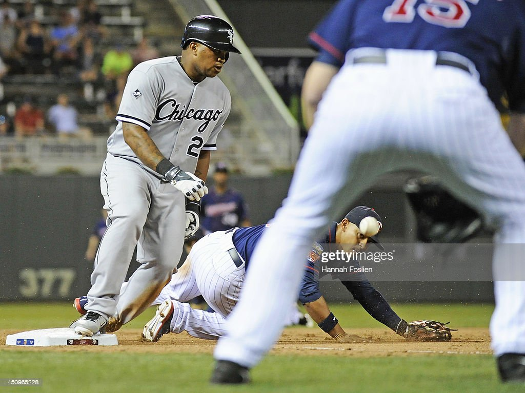 Dayan Viciedo #24 of the Chicago White Sox slides into third base safely as Glen Perkins #15 of the Minnesota Twins backs up teammate Eduardo Escobar #5 as the throw gets past Escobar during the ninth inning of the game on June 20, 2014 at Target Field in Minneapolis, Minnesota. The Twins defeated the White Sox 5-4 with a walk-off.