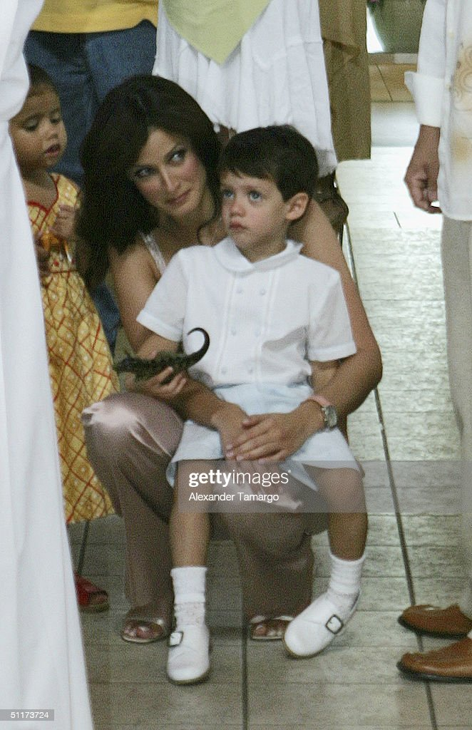 Dayanara Torres holds son Cristian following her son Ryan's baptism ceremony at Saint Agatha's Church on August 14, 2004 in Miami, Florida.