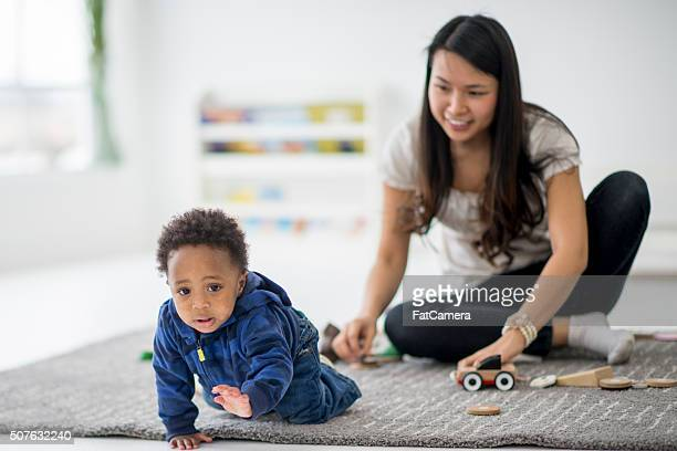 Daycare teacher playing with toddler.