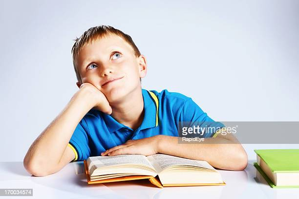 Daydreaming blond boy with books: imagination at work here