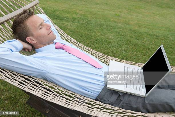 Daydreaming Businessman Relaxing with Laptop in Hammock