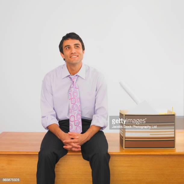 Daydreaming Hispanic businessman sitting on desk with box