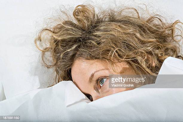 Daydreaming woman in bed under white blanket