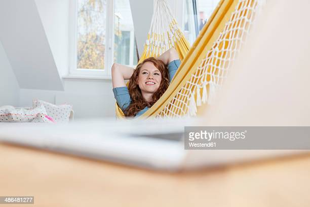 Daydreaming woman relaxing in a hammock in her apartment, laptop in front on a table